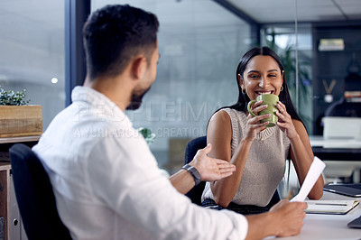 Buy stock photo Shot of two work colleagues reading over some documents together while drinking coffee