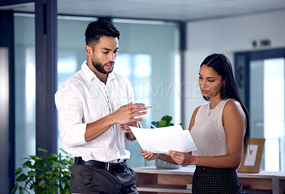 Buy stock photo Shot of two work colleagues reading over some documents together