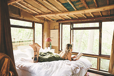 Buy stock photo Shot of a young woman reading a book while lying on a bed in a cabin
