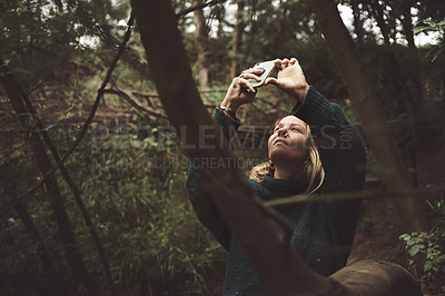 Buy stock photo Shot of a woman using her cellphone to take pictures while out exploring nature