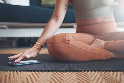 Buy stock photo Closeup shot of an unrecognisable woman using a cellphone while exercising at home