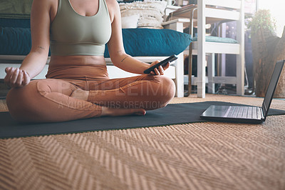 Buy stock photo Closeup shot of an unrecognisable woman using a cellphone and laptop while exercising at home