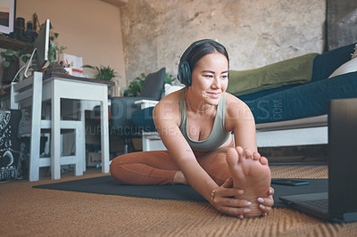 Buy stock photo Shot of a young woman stretching her legs while exercising at home