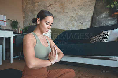 Buy stock photo Shot of a young woman meditating while practising yoga at home