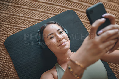 Buy stock photo High angle shot of a young woman wearing headphones and using a cellphone while lying on an exercise mat at home