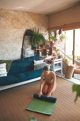 Buy stock photo Shot of a young woman rolling a yoga mat while exercising at home