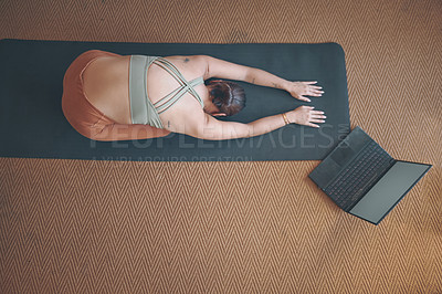 Buy stock photo High angle shot of a young woman using a laptop while practising yoga at home