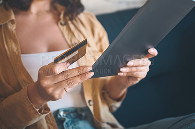 Buy stock photo Shot of an unrecognisable woman using a digital tablet and credit card on the sofa at home