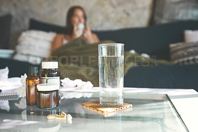 Buy stock photo Shot of a medication on a table with a woman recovering from an illness on the sofa in the background at home