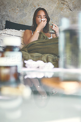 Buy stock photo Shot of a young woman blowing her nose while recovering from an illness on the sofa at home