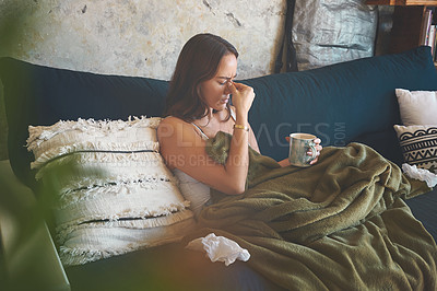 Buy stock photo Shot of a young woman suffering from a headache and feeling sick on the sofa at home