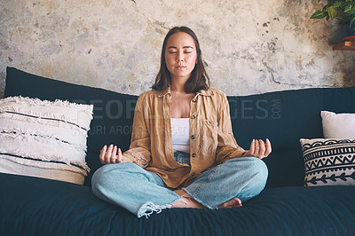 Buy stock photo Shot of a young woman meditating on the sofa at home