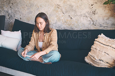 Buy stock photo Shot of a young woman taking a pregnancy test on the sofa at home