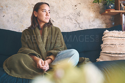 Buy stock photo Shot of a young woman resting under a blanket on the sofa at home