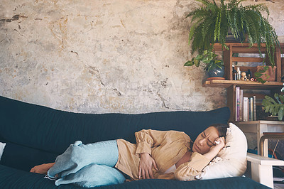 Buy stock photo Shot of a young woman experiencing stomach pain while lying on the sofa at home