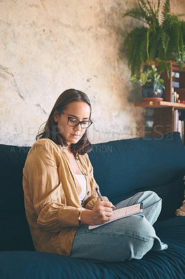 Buy stock photo Shot  of a young woman making notes while relaxing on the sofa at home