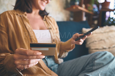 Buy stock photo Shot of an unrecognisable woman using a smartphone and credit card on the sofa at home