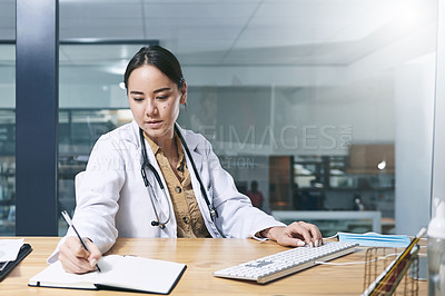 Buy stock photo Shot of an attractive young doctor sitting alone in her office at the clinic and writing in her notebook