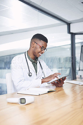 Buy stock photo Shot of a handsome young doctor sitting alone in his office at the clinic and using his digital tablet