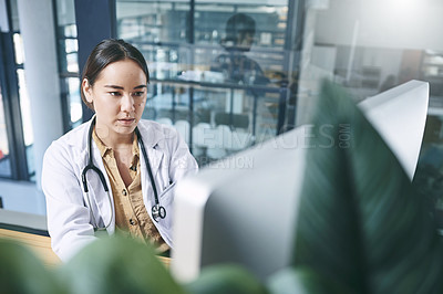 Buy stock photo Shot of an attractive young doctor sitting alone in her office at the clinic and using her computer