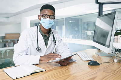 Buy stock photo Shot of a young doctor wearing a face mask and sitting in his office at the clinic while using technology