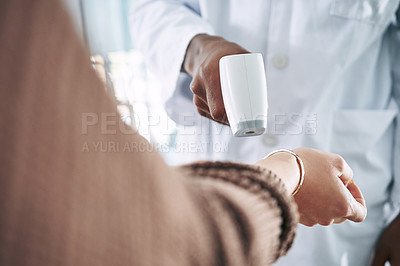 Buy stock photo Cropped shot of an unrecognizable doctor standing with a patient in the clinic while taking her temperature