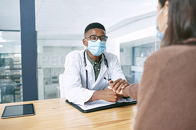Buy stock photo Shot of a young doctor sitting with his patient and wearing a face mask while comforting her in the clinic