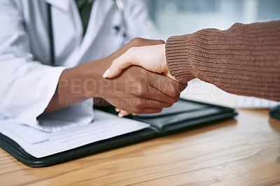 Buy stock photo Cropped shot of an unrecognizable doctor sitting and shaking hands with his patient during a consultation in the clinic