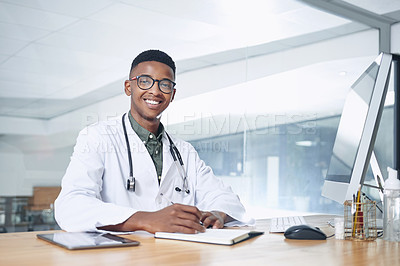 Buy stock photo Shot of a handsome young doctor sitting alone in his office at the clinic and using his notebook