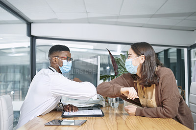 Buy stock photo Shot of a young doctor sitting with his patient and greeting her with an elbow bump in the clinic