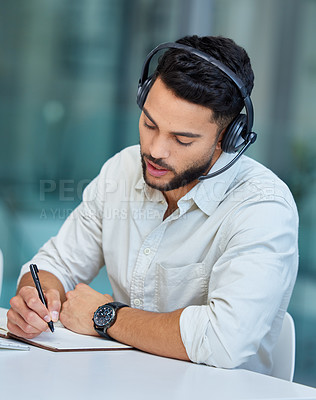 Buy stock photo Shot of a young businessman making notes while working in a call center