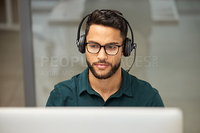 Buy stock photo Shot of a businessman using a computer while working in a call center