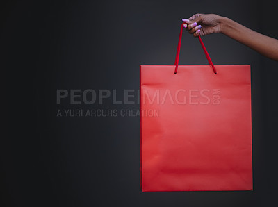 Buy stock photo Closeup shot of a woman holding a shopping bag against a dark background