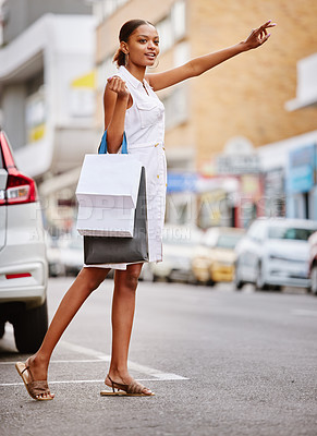 Buy stock photo Shot of a young woman hailing a cab while holding shopping bags
