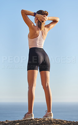 Buy stock photo Rearview shot of an unrecognizable and athletic young woman standing with her hands behind her head during her run in the mountains
