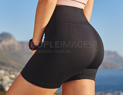 Buy stock photo Closeup shot of an unrecognizable and athletic young woman in running shorts taking a break during her run in the mountains