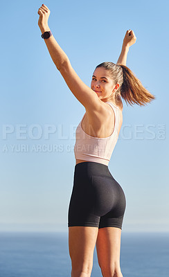 Buy stock photo Cropped portrait of an attractive and athletic young woman standing with her arms raised during her run in the mountains