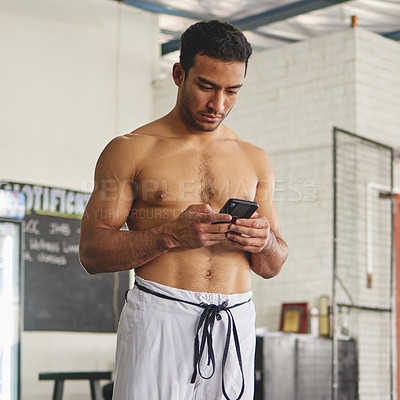 Buy stock photo Cropped shot of a handsome young man standing using his phone while standing shirtless in his jiu jitsu pants in the gym
