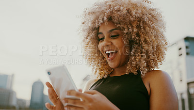 Buy stock photo Shot of an attractive young woman standing alone and looking surprised while using her cellphone in the city