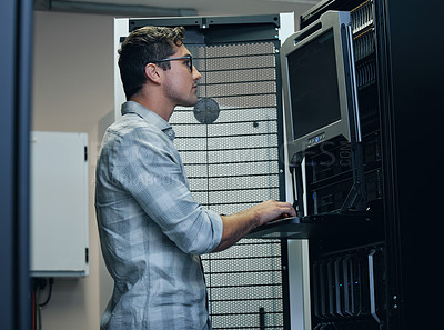 Buy stock photo Cropped shot of a handsome young male programmer working on a computer in a server room