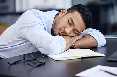 Buy stock photo Shot of an exhausted businessman having a quick nap on the desk at work