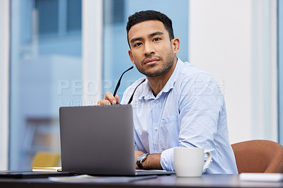 Buy stock photo Shot of a handsome young businessman sitting alone in his office and using his laptop