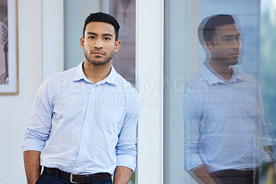 Buy stock photo Shot of a handsome young businessman standing alone in the office during the day
