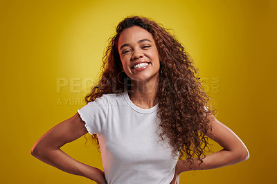Buy stock photo Studio portrait of a young woman posing against a yellow background