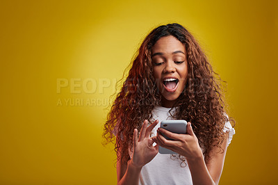 Buy stock photo Studio shot of a young woman using a cellphone against a yellow background