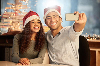 Buy stock photo Shot of two young businesspeople taking a selfie while celebrating Christmas at work