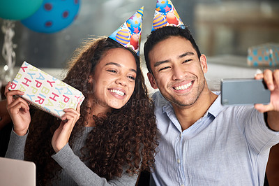 Buy stock photo Shot of two young businesspeople taking a selfie while celebrating a birthday at work