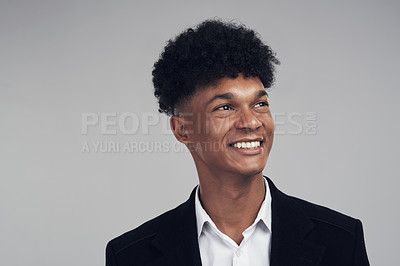 Buy stock photo Studio shot of a young businessman looking away thoughtfully against a grey background