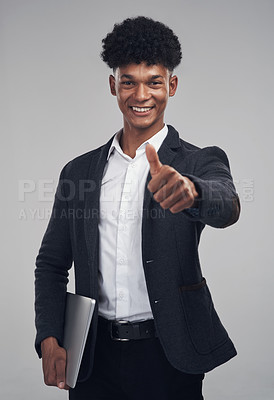 Buy stock photo Studio shot of a young businessman showing thumbs up against a grey background