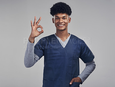 Buy stock photo Shot of a male nurse showing the ok sign while standing against a grey background